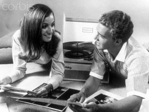 1960s TEEN COUPLE PLAYING LP VINYL RECORDS ON PORTABLE PHONOGRAPH